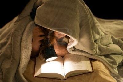 4408996-una-giovane-ragazza-leggendo-un-libro-sotto-le-coperte-con-una-torcia